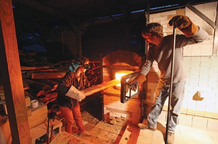 Bendo takes a turn stoking the kiln, as the internal temperature climbs toward 2,380 degrees.