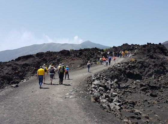 L'immagine raffigura un gruppo di persone che si dirige verso la cima dell'Etna