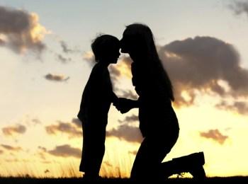 La foto mostra le sagome di una madre che bacia il figlio