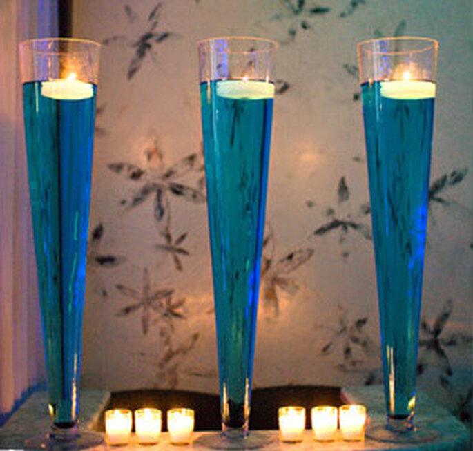 Floreros decorados con liquido azul y velas flotantes blancas