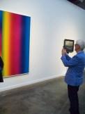 Simon Durivage photographiant une oeuvre, incluant du bleu éclatant comme son veston!