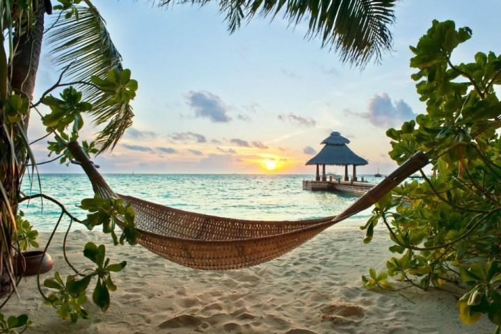 Amaca sulla spiaggia di un atollo maldiviano al tramonto
