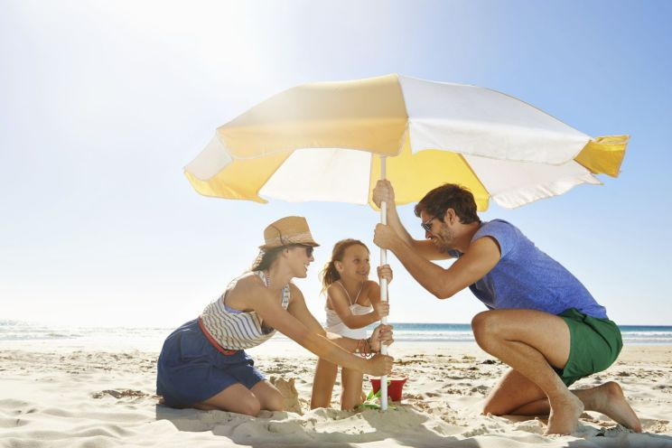 Shot of a young family setting up an umbrella on a beach
