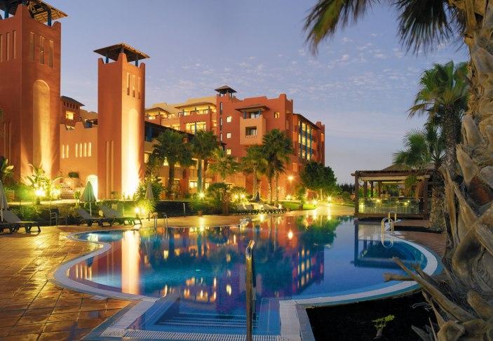 Vista general nocturna del hotel y la piscina