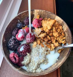Vegan breakfast recipe: Pouring almond milk into a coconut bowl filled with chia pudding, vegan granola, and frozen berries