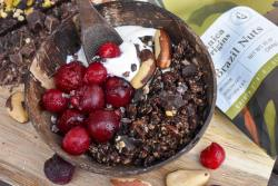 chocolate granola, yogurt, cherries, and brazil nuts piled into a coconut bowl with nuts and granola and cherries surrounding in the background