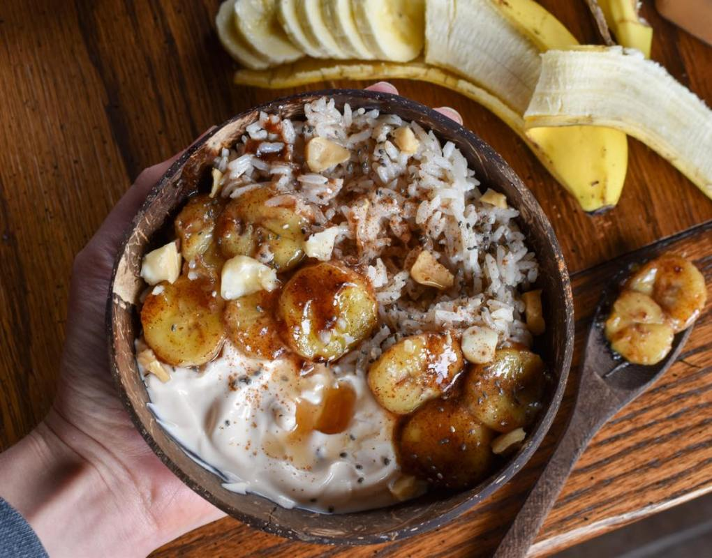 hand holds a coconut vegan breakfast bowl filled with warmed rice, non dairy yogurt, and caramelized banana. Brown wooden table and sliced banana are shown in the background