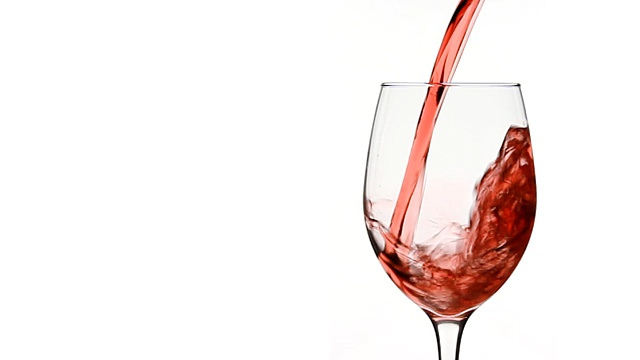 pouring red wine into a glass