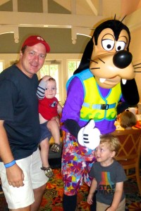 Goofy dressed in beach ware with a father and 2 little boys