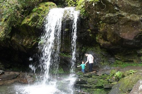 Boy and man walking behind Grotto Falls