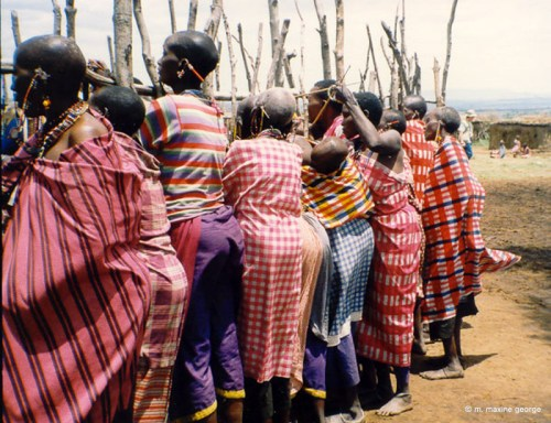 Women in colourful sheets gather around corral offering to trade beadwork to tourists in Kenya