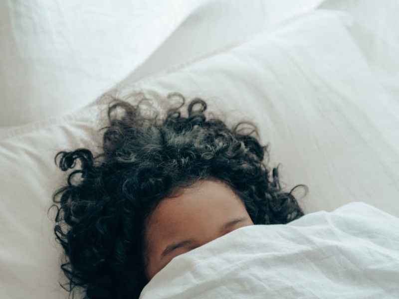 unrecognizable person sleeping under blanket