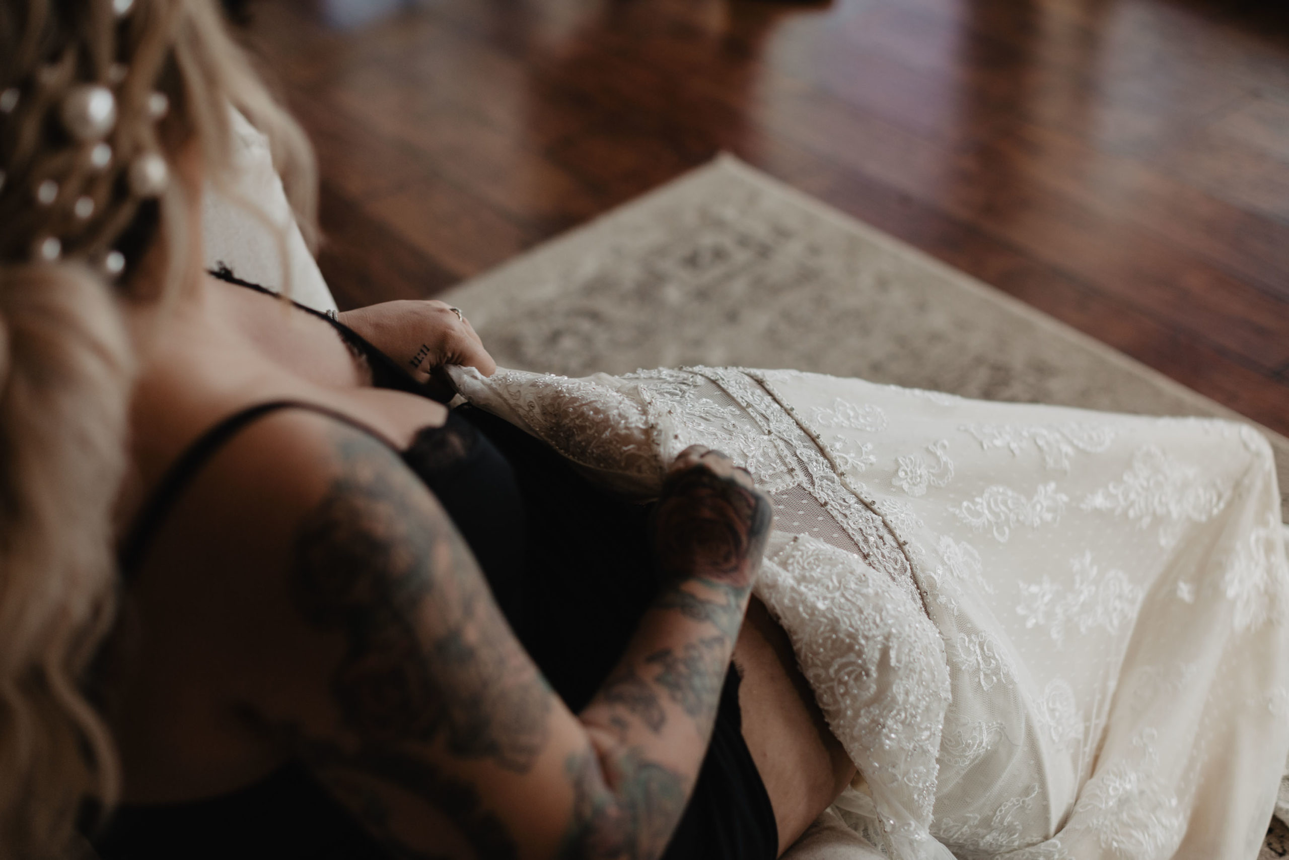 tattooed bride putting on wedding dress
