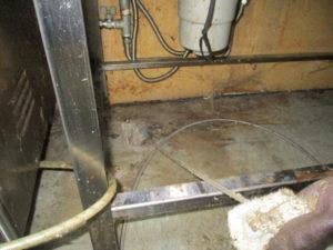 排水管を高圧洗浄機に取り付けたスズラン付きホースで洗浄中