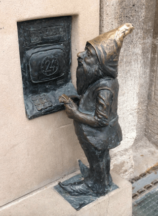 Dwarf using ATM on side of bank building