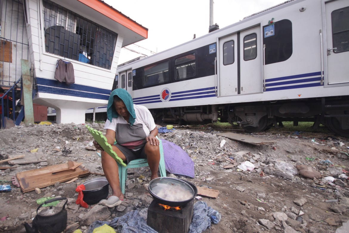 Homeless person dangerously cooks by the railway