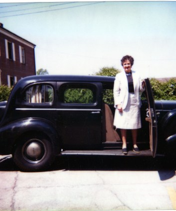 Patricia Cummins standing in front of Arms 1937 Buick, May 21, 1981 prior to its leaving for its new owner, H. C. Roberts. Weller House visible in background. Photographer:  MVHS Staff