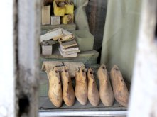 Through the metal bars and glass, you can see old materials used in shoe-making