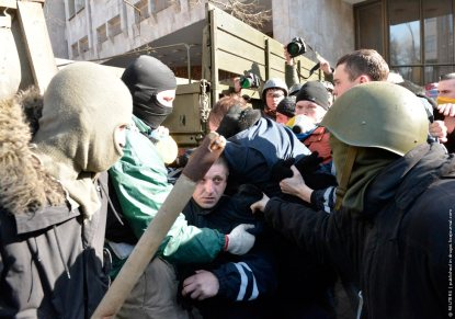 Anti-government protesters escort Interior Ministry members after attacking an office of the pro-presidential Party of the Regions in Kiev
