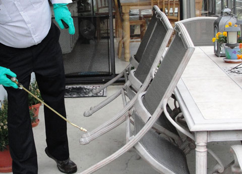 image of a pest control worker spraying under a table and chairs for spiders on an outdoor patio