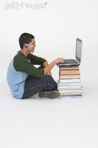 Side profile of a teenage boy sitting in front of a stack of books and using a laptop