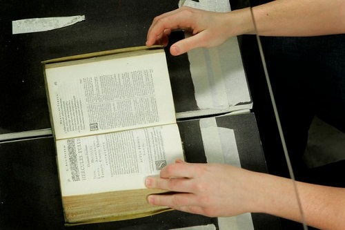 A librarian in Ann Arbor, Mich., using a desktop machine to digitize a rare, centuries-old Bible.