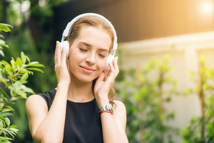 image of a woman listening to music using headphones