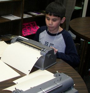 Blind boy using Braille embosser
