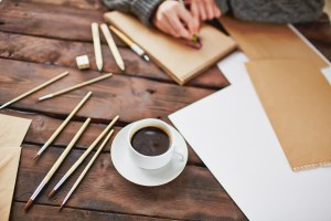Image of coffee cup pens and notebooks.