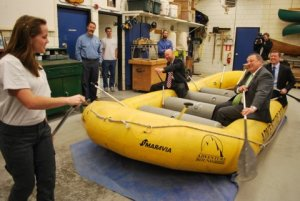 A student instructs John Nass, Education Commissioner Stephen Bowen and Gov. Paul LePage in a raft on a shoproom floor.