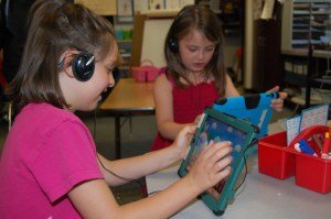 Sara Richard and Lauren Fletcher use their iPads to learn letters and to spell words.