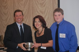 Education Commissioner Stephen Bowen congratulates 2013 Teacher of the Year Shannon Shanning, pictured with a former student, at celebratory banquet.