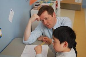 East End kindergartner Antonio Hernandez explains his math journal to Commissioner Bowen.