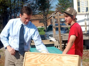 Ken Stump, eighth grader at Oxford Hills Middle School, shows Commissioner Bowen a solar panel students created to heat the indoor greenhouse at Roberts Farm in Norway.