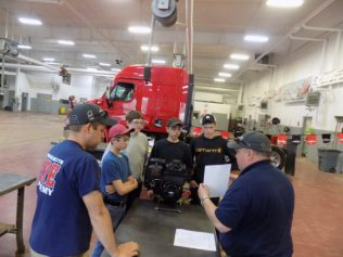 Ashland High School Students and managers for FFA Agricultural Technology & Mechanical Systems event at Small Engines Troubleshooting station. Event Judge Tyler Raymond on left with his father Dan Raymond, Caribou on right. Dan was later awarded with the Maine FFA State Degree, the highest possible distinction from a state association. Photo by UpNorth Motorsports.