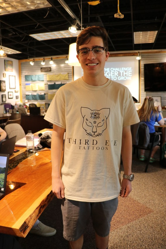 UTC student Josiah Brochu wearing a t-shirt bearing his self-designed logo