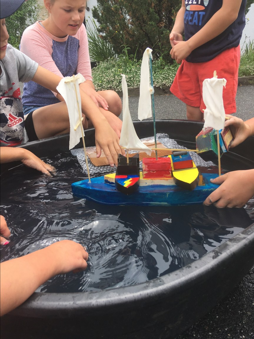 students outside working together with model boat