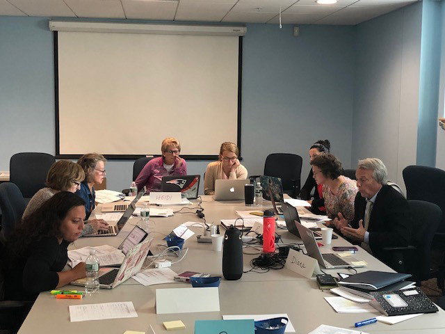 Educators working together at a conference table with laptops