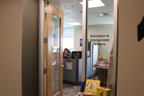 The entrance way to the office of the Education in Unorganized Territories (EUT) where EUT staff member Cathy Severance can be seen sitting at her desk.