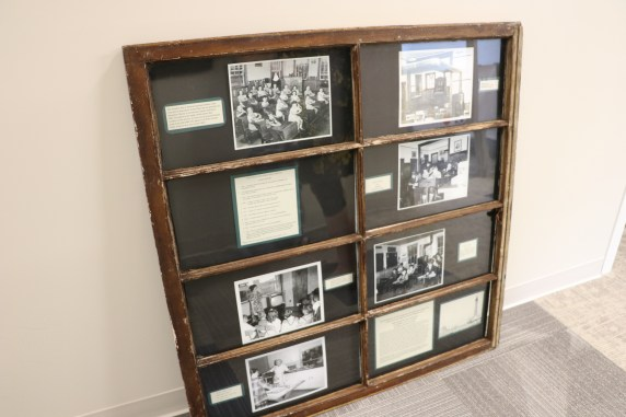 Black and white photos taken in unorganized territories, now on display in an old window frame from an EUT school at the Maine DOE.