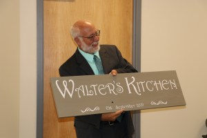 Walter Beesley holds up the new kitchen sign dedicating the space to him for his efforts to launch the classroom.