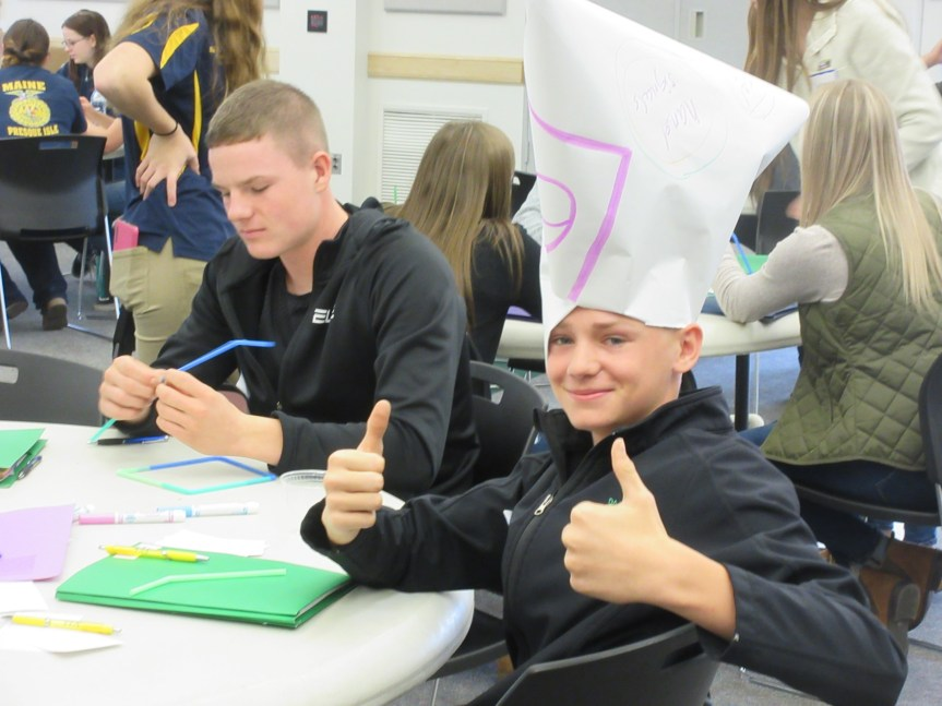 FFA Officers rise to the challenge of putting creative leadership into practice. Lane McCrum (right), grade 9, Mars Hill, models unusual headgear intended to promote recycling, with Mars Hill senior Brayden Bradbury on left.