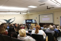 presenter talking to a room full of educators with projector displaying text.