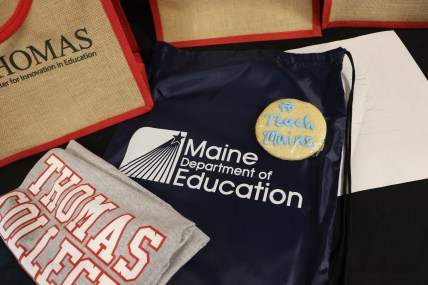 t-shirt, backpack and cookie with Thomas college and Maine DOE logos.