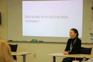 """educator sitting talking to students with an over head that says, """"How to we make sure we create a welcoming environment?"""""""