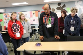 students and teacher standing looking at a robot
