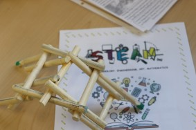 "stick bridge with paper underneath that says, ""STEAM"""