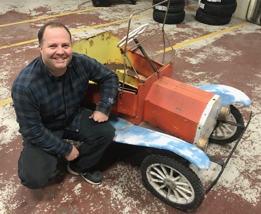 Patrick Penley crouches next to his repaired clown car that he brought back to life thanks to the help of a Lewiston Adult Education class