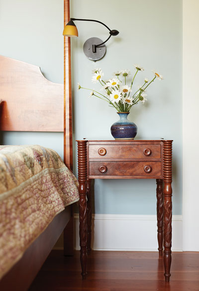 night stand in bedroom with flowers in a vase on it