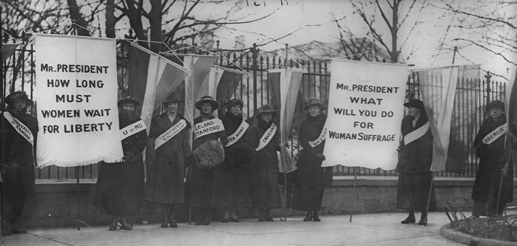 "Women picket outside the White House with signs reading ""Mr. President How Long Must Women Wait for Liberty"" and ""Mr. President what will you do for woman suffrage"""